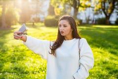 Schönes Brunettemädchen, das ein Selbstporträt im Park bei Sonnenuntergang nimmt lizenzfreie stockbilder