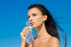 Schönes Brunettemädchen, das eine Flasche Wasser anhält Lizenzfreies Stockfoto