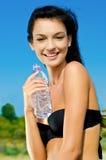 Schönes Brunettemädchen, das eine Flasche Wasser anhält. Stockfoto