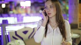 Schönes Brunettemädchen, das an einem Handy in einem Einkaufszentrum spricht stock video footage