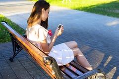 Schönes Brunettemädchen, das einen Mitteilungstelefonpark sitzt auf Bank in Kleid, entspannende Sommertagesgeschäftsfrau schreibt stockfotografie
