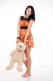 Schönes Brunettemädchen, das einen Teddybären hält Lizenzfreie Stockfotografie