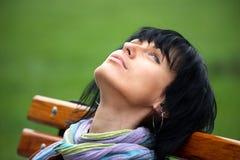 Schönes Brunettemädchen, das in einer Parkbank stillsteht lizenzfreies stockfoto