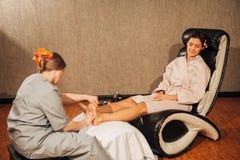 Schönes Brunettemädchen, das Fußmassage tut therapeutisch Stockfotos