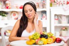 Schönes Brunettemädchen, das am Küchentisch mit einer Platte der frischen Frucht sitzt Stockbilder