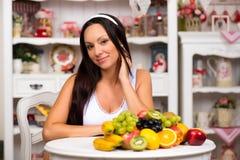 Schönes Brunettemädchen, das am Küchentisch mit einer Platte der frischen Frucht sitzt Diät, gesundes Lebensmittel und Vitamine Lizenzfreie Stockbilder