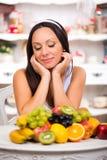 Schönes Brunettemädchen, das mit einer Platte der frischen Frucht sitzt Stockfotos