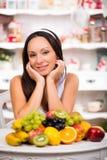 Schönes Brunettemädchen, das mit einer Platte der frischen Frucht sitzt Diät, gesundes Lebensmittel und Vitamine Stockfotografie