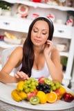 Schönes Brunettemädchen, das mit einer Platte der frischen Frucht sitzt Diät, gesundes Lebensmittel und Vitamine Stockbild