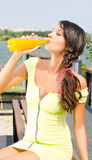 Schönes Brunettemädchen, das Orangensaft von einer Plastikflasche trinkt. Lizenzfreies Stockbild