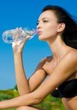 Schönes Brunettemädchen, das von einer Flasche von trinkt Stockbilder