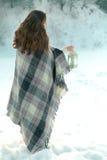 Schönes Brunettemädchen in einem gestrickten Schal eingewickelt im Plaid und im Halten einer Weihnachtslaterne Stockfotos