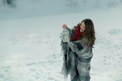 Schönes Brunettemädchen in einem gestrickten Schal eingewickelt im Plaid und im Halten einer Weihnachtslaterne Stockbilder