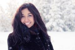 Schönes Brunettemädchen in einem Pelzmantel auf Hintergrund eines Winterwaldes stockfotos