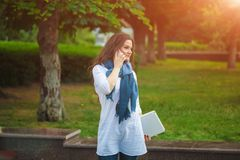 Schönes Brunettemädchen in einem Schal auf der Straße sprechend am Telefon, das einen Laptop hält stockbild