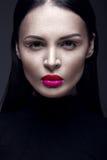 Schönes Brunettemädchen in einem schwarzen Kleid, in einem geraden Haar und in einem modischen Make-up Zauberschönheitsgesicht lizenzfreie stockfotografie
