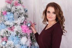 Schönes Brunettemädchen in einer roten Strickjacke steht nahe einem Baum herein lizenzfreies stockfoto