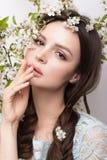 Schönes Brunettemädchen im blauen Kleid mit einem leichten romantischen Make-up, rosa Lippen und Blumen Die Schönheit des Gesicht stockfotos