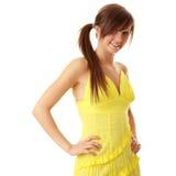 Schönes Brunettemädchen im gelben Kleid. Lizenzfreies Stockfoto