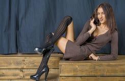 Schönes Brunettemädchen im netten Lächeln Hamming der schwarzen Strümpfe stockfoto