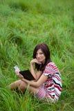 Schönes Brunettemädchen im Parklesebuch Stockfotos