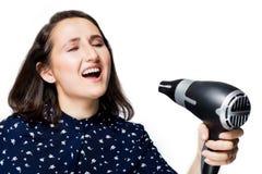 Schönes Brunettemädchen mit Augen schloss das Schreien, in ein Isolat Hairdryer die blauen Hemdglückgefühle an Hand singend stockfotos