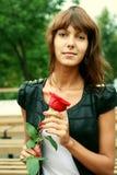 Schönes Brunettemädchen mit der Knospe der Rose lizenzfreie stockfotografie