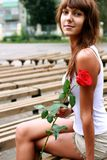 Schönes Brunettemädchen mit der Knospe der Rose stockfotos