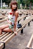 Schönes Brunettemädchen mit der Knospe der Rose lizenzfreies stockfoto