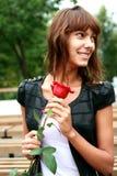 Schönes Brunettemädchen mit der Knospe der Rose lizenzfreies stockbild