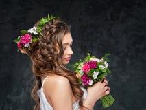 Schönes Brunettemädchen mit einer Zusammensetzung von Blumen Stockfotos