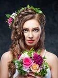 Schönes Brunettemädchen mit einer Zusammensetzung von Blumen Stockbilder