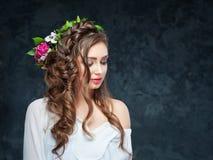 Schönes Brunettemädchen mit einer Zusammensetzung von Blumen Stockfoto