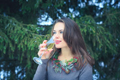 Schönes Brunettemädchen mit Glas Champagner draußen am Winterabend Lizenzfreies Stockfoto