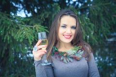 Schönes Brunettemädchen mit Glas Champagner draußen am Winterabend Lizenzfreie Stockbilder