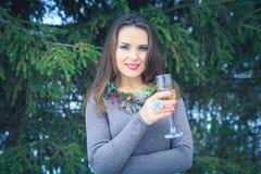 Schönes Brunettemädchen mit Glas Champagner draußen am Winterabend Stockfotografie