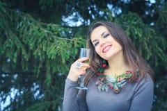 Schönes Brunettemädchen mit Glas Champagner draußen am Winterabend Stockfoto
