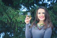 Schönes Brunettemädchen mit Glas Champagner draußen am Winterabend Stockbild