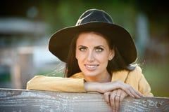 Schönes Brunettemädchen mit Landblick nahe einem alten Bretterzaun Attraktive Frau mit schwarzem Hut und gelbem Mantel stockfotos