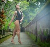 Schönes Brunettemädchen mit perfektem Körper im Badeanzug im Park auf dem Bali Stockfotos