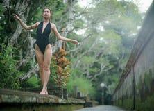 Schönes Brunettemädchen mit perfektem Körper im Badeanzug im Park auf dem Bali Lizenzfreie Stockfotografie