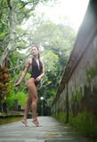 Schönes Brunettemädchen mit perfektem Körper im Badeanzug im Park auf dem Bali Stockbild