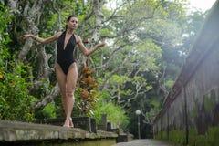 Schönes Brunettemädchen mit perfektem Körper im Badeanzug im Park auf dem Bali Lizenzfreie Stockbilder