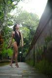 Schönes Brunettemädchen mit perfektem Körper im Badeanzug im Park auf dem Bali Stockfotografie