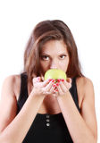 Schönes Brunettemädchen schnüffelt grünen Apfel Stockfotografie