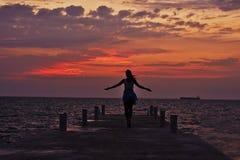 Schönes Brunettemädchen trifft den Sonnenaufgang auf dem Pier Stockbild