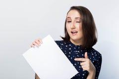 Schönes Brunettemädchen zeigt einen Finger auf einem sauberen Weißbuch, blinzelt mit einem Lächeln, Glück, Freude, Stockbild