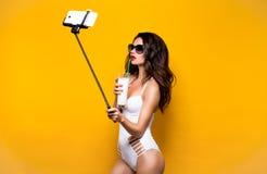 Schönes Brunettemodell in der Sonnenbrille und in weißem monokini, die selfie mit Zelle auf selfiestick beim Trinken des Cocktail stockfoto
