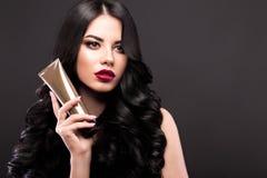 Schönes Brunettemodell: Locken, klassisches Make-up und rote Lippen mit einer Flasche Haarpflegemitteln Das Schönheitsgesicht lizenzfreie stockfotos