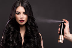 Schönes Brunettemodell: Locken, klassisches Make-up und rote Lippen mit einer Flasche Haarpflegemitteln Das Schönheitsgesicht stockbilder